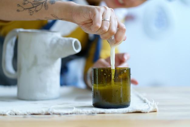젊은 여성 예술가가 물과 스폰지를 사용하는 원시 점토 손의 도자기 세라믹을 성형하고 성형합니다