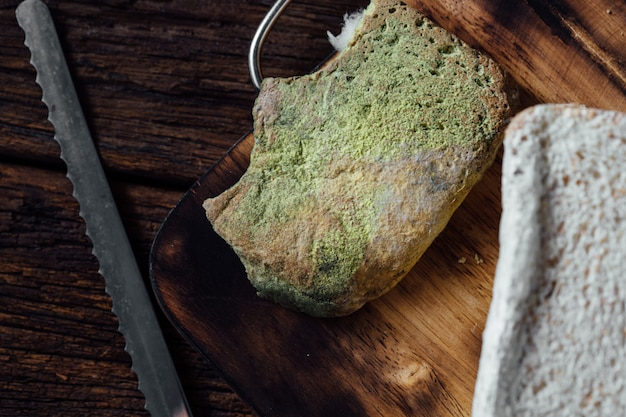Moldy bread on wooden table