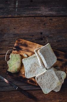 Moldy bread on wooden table