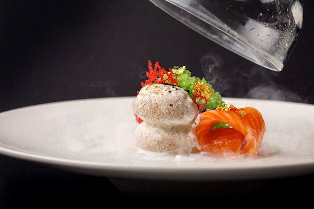 Molecular cuisine gravlax trout with garlic ice cream on a black background