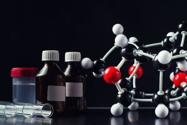 Molecular formula and laboratory equipment on a dark background close up.