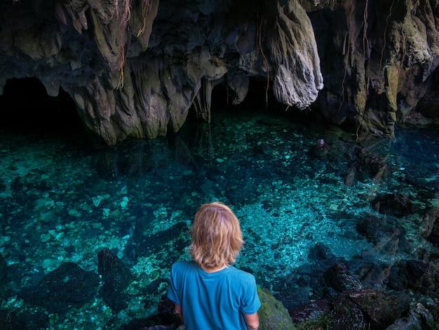 洞窟の中の自然の湖の女。カラフルな反射、青緑色の透明な水、夏の冒険。観光地、ケイ島、moluccas、インドネシア。