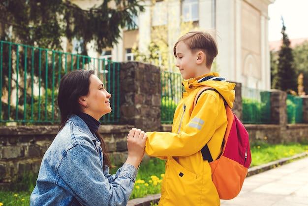 お母さんは子供を学校に連れて行きます。ランドセルを持ってファーストクラスで学校に行く手をつないでいる母と生徒。学校のコンセプトに戻ります。母は一年生の小さな男子生徒を率いています。