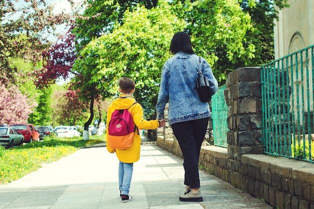 お母さんは子供を学校の母親に連れて行き、生徒はファーストクラスで学校に行く手を握っています