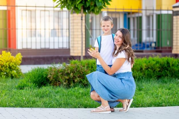 Мама провожает ребенка сына с рюкзаком в школу или детский сад, а затем обратно в школу.