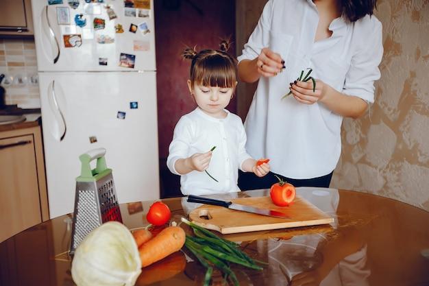母親はキッチンで自宅で野菜を料理する
