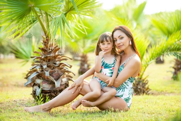 열대 야자수와 꽃에서 여름에 동일한 수영복을 입은 엄마와 3 살짜리 작은 딸. 수영복과 스타일.