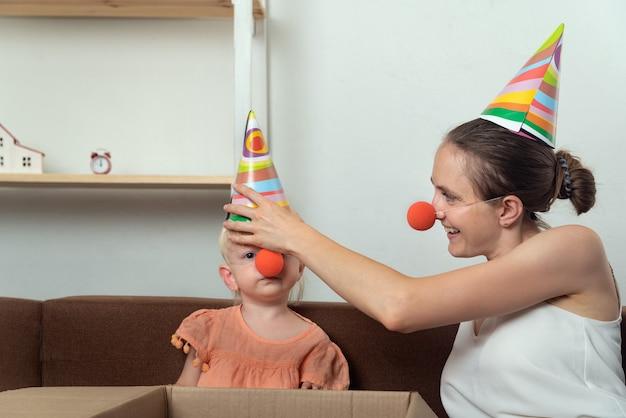 엄마와 아기는 휴가를 준비하고 있습니다. 엄마는 어린 딸을 위해 파티 모자와 광대 코를 씁니다.