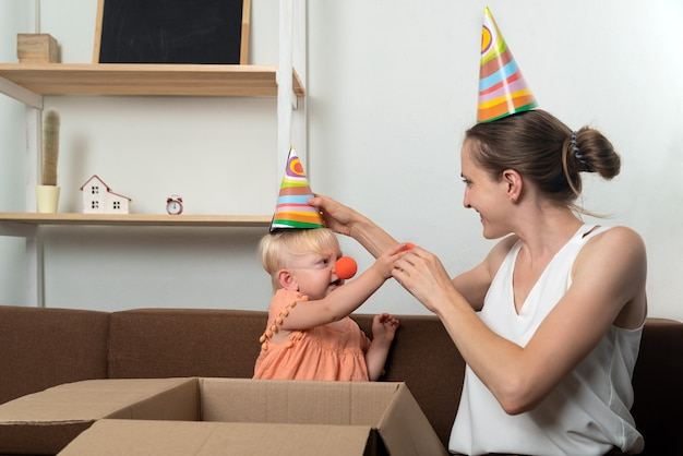 엄마와 아기는 휴가를 준비하고 있습니다. 작은 딸을위한 파티 모자와 광대 코.