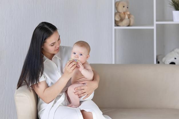 Мама и малыш сидят на диване, ребенок кусает игрушку.