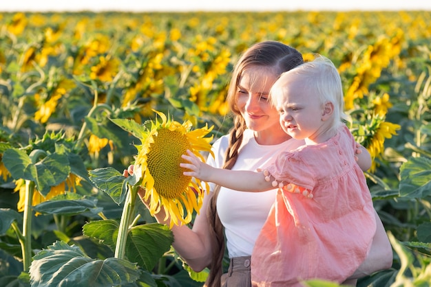ママと赤ちゃんはひまわり畑を歩いています