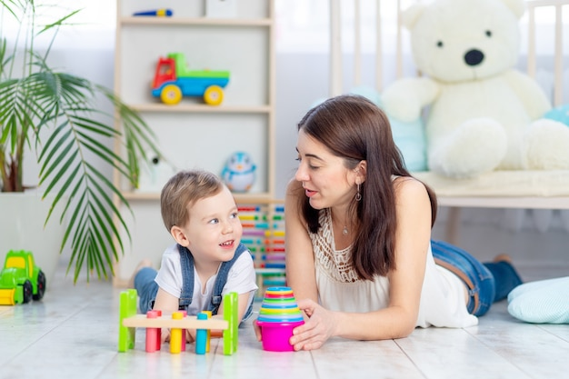 ママと男の子は子供部屋で教育玩具で家で遊んでいます。幸せで愛情のある家族。