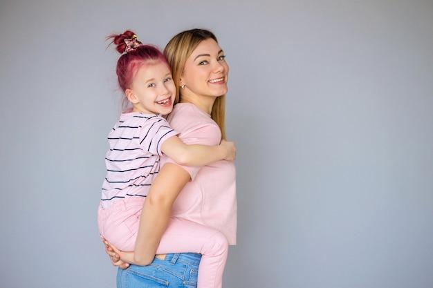 회색 배경 스튜디오 초상화에 고립 된 엄마와 아기 딸. 어머니의 날 사랑 개념 어린 시절 가족