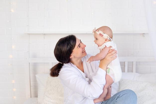 엄마와 아기 소녀는 집에서 하얀 면 침대에 앉아 포옹하고 키스하고, 모성애와 보살핌