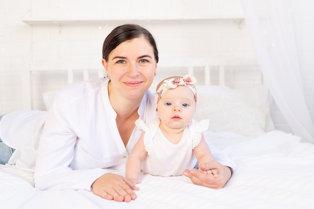 집에서 하얀 면 침대에 누워 있는 엄마와 아기 소녀, 모성애와 보살핌