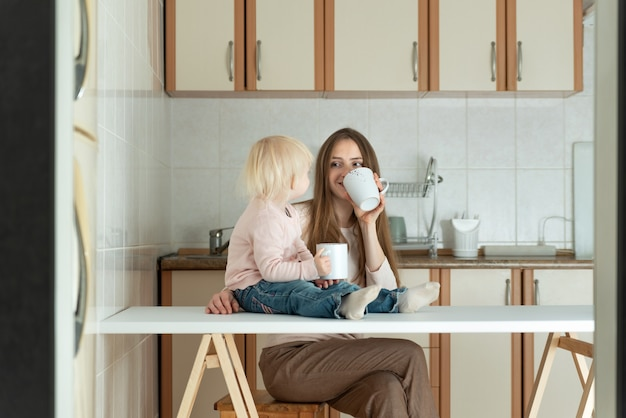 Мама и малыш утром завтракают на кухне. счастливая молодая семья.