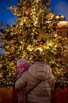 그녀의 팔에 엄마와 아기는 거리 공정한 후면보기에서 빛나는 크리스마스 트리를 봅니다