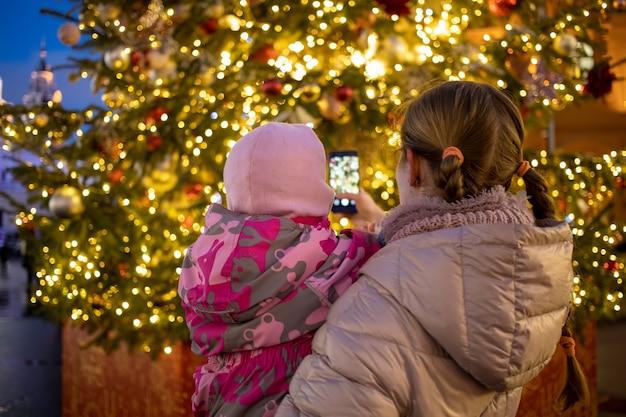 Мама и ребенок на руках фотографируют елку на уличной ярмарке. вид сзади.