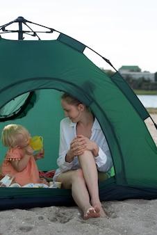 캠프장에서 관광 텐트에서 엄마와 아기 놀이