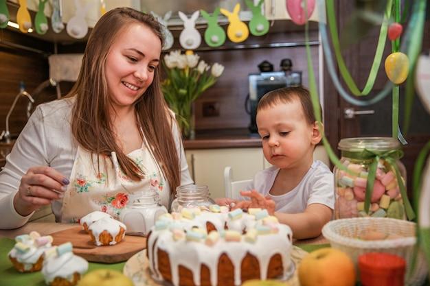 ママと赤ちゃんの息子は、装飾されたキッチンのテーブルで自宅でイースターケーキを飾ります
