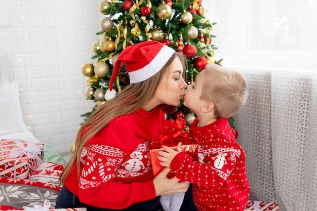 빨간 스웨터와 모자를 쓴 엄마와 아기 아들은 크리스마스 트리 아래에서 선물을 주고 집에서 침대에서 서로 축하하는 키스를 하고 새해와 크리스마스를 기뻐합니다