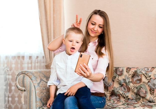 居心地の良いリビングルームで自分撮りをしているママと赤ちゃん。ママと息子は変な顔をして、カメラで自分の写真を撮ります