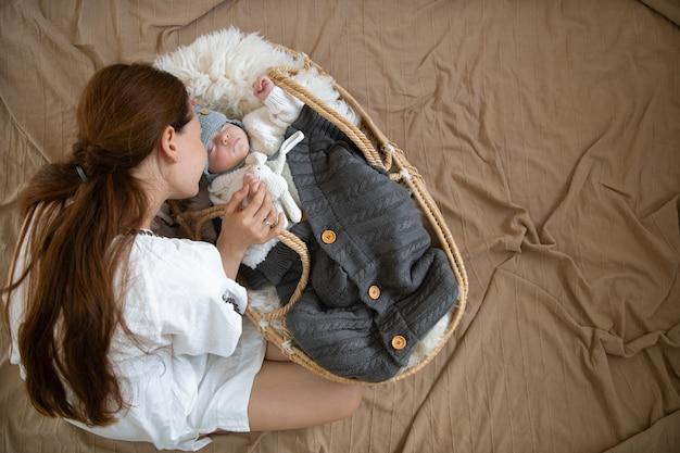따뜻한 담요 아래 따뜻한 니트 모자를 쓰고 고리 버들 요람에서 달콤하게 잠자는 엄마와 아기.