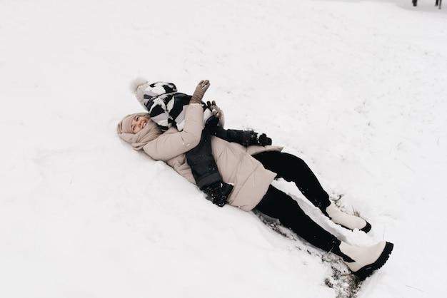 Мама и мальчик лежат весело в снегу, активный образ жизни, зима, семья