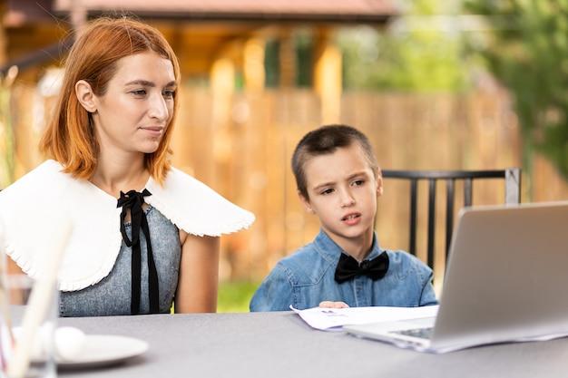 Мама и мальчик-школьник занимаются уроками через ноутбук дома в саду. интернет-классы для детей. школьник слушает лекцию и решает задачи
