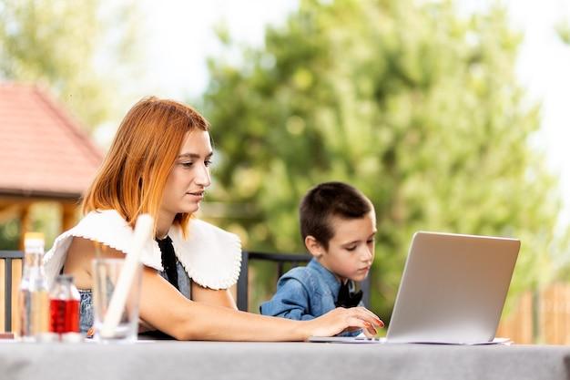 엄마와 소년 남학생은 정원에 있는 집에서 노트북을 통해 수업에 참여하고 있습니다. 어린이를 위한 온라인 수업. 남학생은 강의를 듣고 문제를 해결합니다.