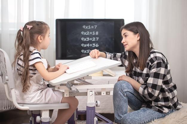 엄마와 아이는 수학 숙제를하고 있습니다. 홈 스쿨링 및 교육 개념.