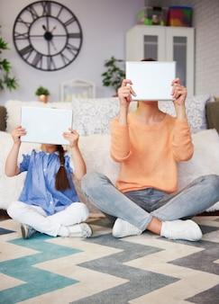 Мама и ребенок, держа планшет перед лицом