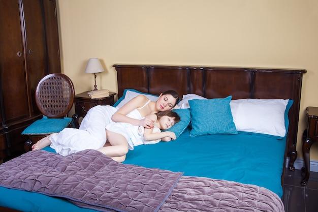 Мама и ребенок обнимаются и спят вместе. студийный снимок