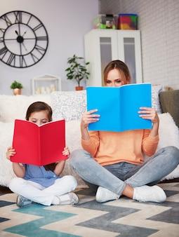 Мама и ребенок читают книгу в гостиной