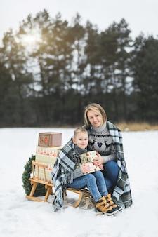 Мама и ребенок сидят вместе на деревянных украшенных санях с рождественскими подарками