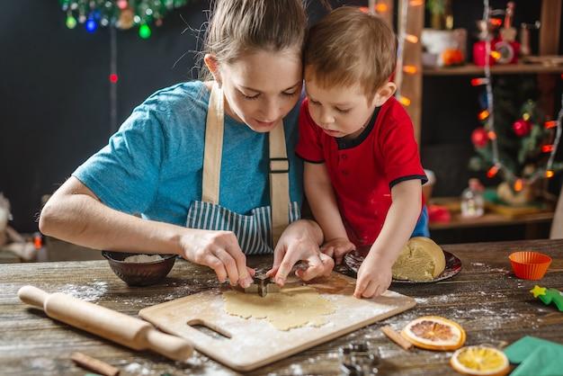 엄마와 아이의 아들은 수제 휴일 진저를 굽기 위해 반죽을 형성합니다.
