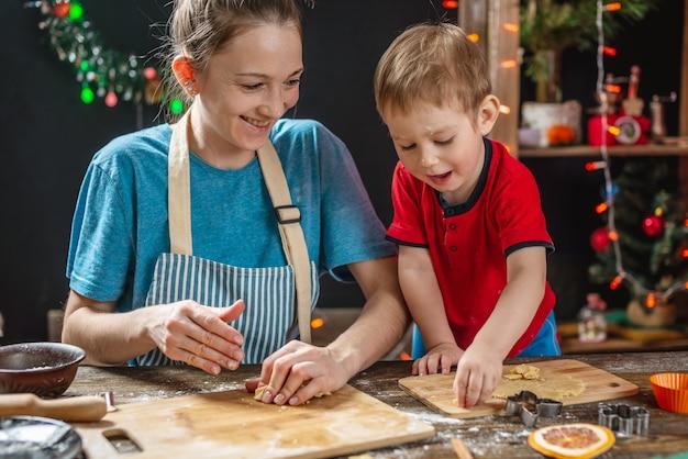 Мама и ребенок-сын лепят тесто для выпечки домашних праздничных пряников