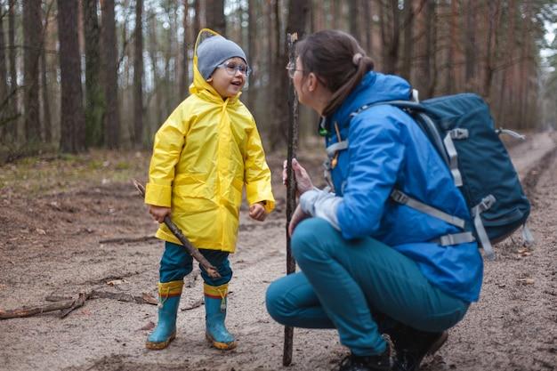 レインコートを着て雨が降った後、ママと子供が一緒に林道を歩く