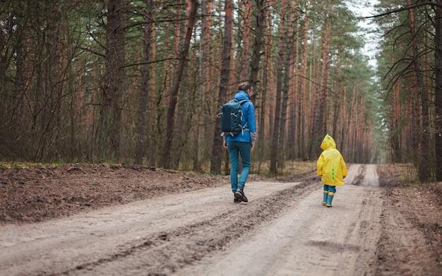 一緒にレインコートで雨が降った後、林道を歩いているママと子供、背面図