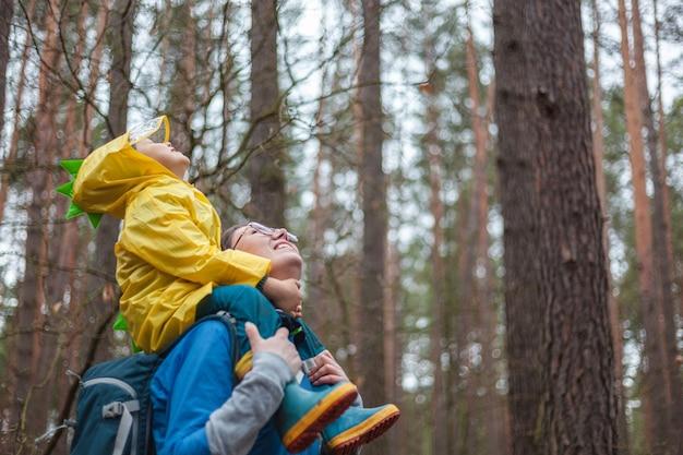 一緒にレインコートで雨が降った後、森の中を歩くママと子供