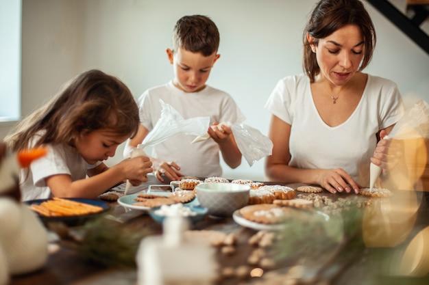 ママと子供たちは家でクリスマスのジンジャーブレッドを飾ります男の子と女の子はsugでコルネットでペイントします...