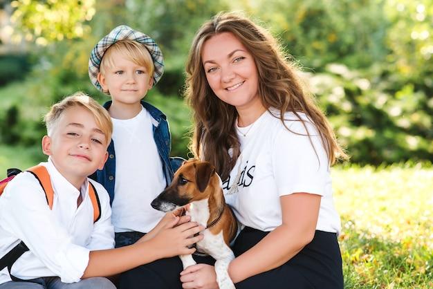 엄마와 아이들은 야외에서 강아지와 함께 연주 재미. 화창한 날에 공원에서 즐기는 행복 한 가족. 소유자와 산책하는 작은 강아지 잭 러셀 테리어. 아이들과 개는 가장 친한 친구입니다.