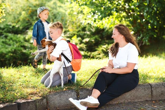 엄마와 아이들은 야외에서 개와 함께 즐겁게 놀고 있습니다. 화창한 날에 공원에서 즐기는 행복한 가족. 작은 강아지 잭 러셀 테리어가 주인과 함께 걷고 있습니다. 아이들과 개는 가장 친한 친구입니다.