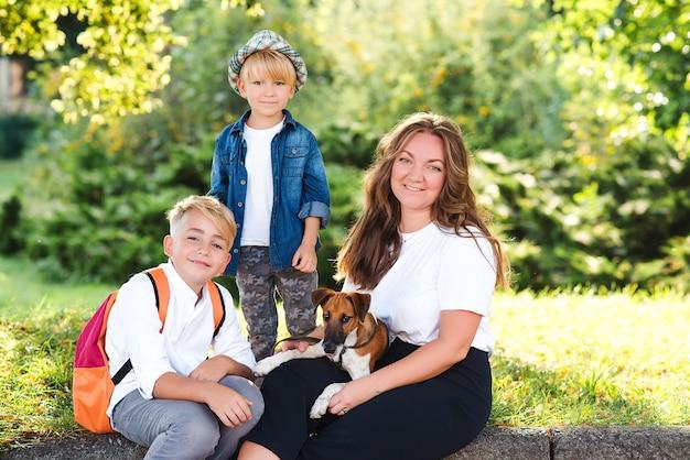 엄마와 아이들은 야외에서 개와 즐겁게 놀고 있습니다. 화창한 날 공원에서 즐기는 행복한 가족. 작은 강아지 잭 러셀 테리어가 주인과 함께 걷고 있습니다. 아이들과 개는 가장 친한 친구입니다.