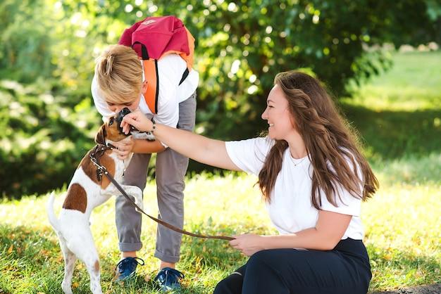 엄마와 아이들은 야외에서 개와 함께 즐겁게 놀고 있습니다. 화창한 날에 공원에서 즐기는 행복한 가족. 주인과 산책하는 작은 강아지 잭 러셀 테리어