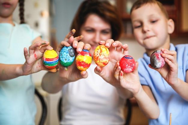 엄마와 아이들은 부활절을 위해 페인트 칠한 달걀을 보여줍니다.