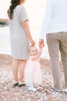 엄마와 아빠는 빌라 마일로세르 근처 해변에 서 있는 어린 소녀를 안고 있습니다.