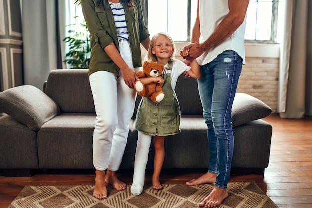 Мама и папа помогают маленькой дочке со сломанной ногой с реабилитацией, учат снова ходить.