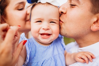 Mom and dad kiss tender little smiling girl in blue dress