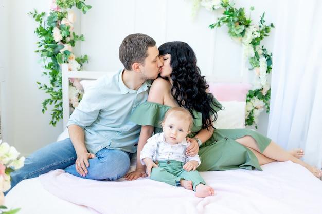 Мама и папа целуются, ребенок на руках, концепция счастливой семьи, день семьи